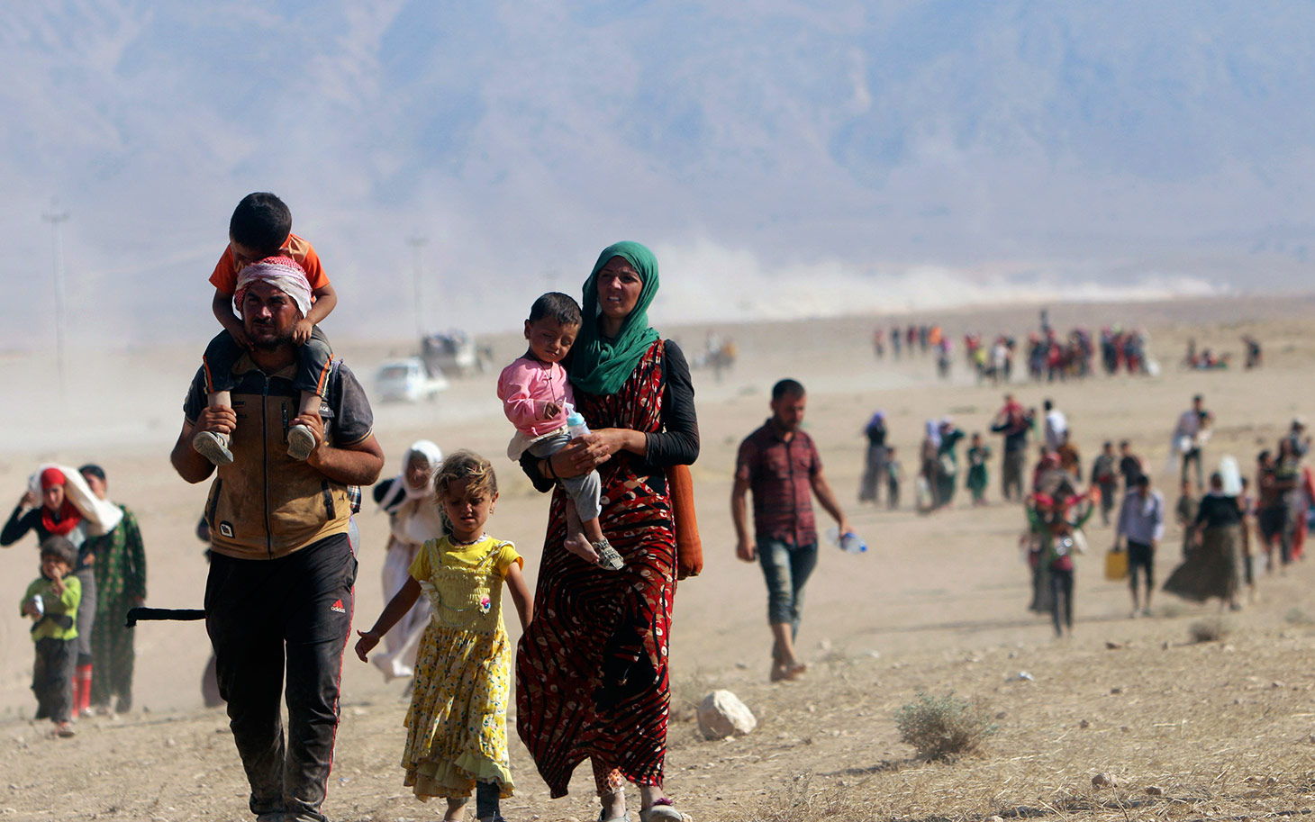 Displaced people from the minority Yazidi sect, fleeing violence from forces loyal to the Islamic State in Sinjar town, walk towards the Syrian border, on the outskirts of Sinjar mountain, near the Syrian border town of Elierbeh of Al-Hasakah Governorate