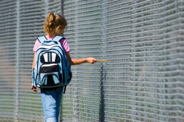 Little girl walking to school by school fence on beautiful sunny day wth back pack and pencil